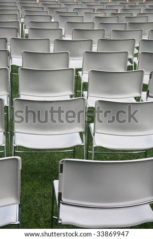 Plastic chairs set up on green grass background