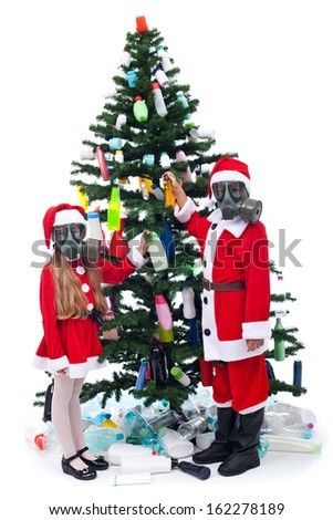 Plastic Christmas - environmental concept with kids decorating the tree using colorful bottles - stock photo