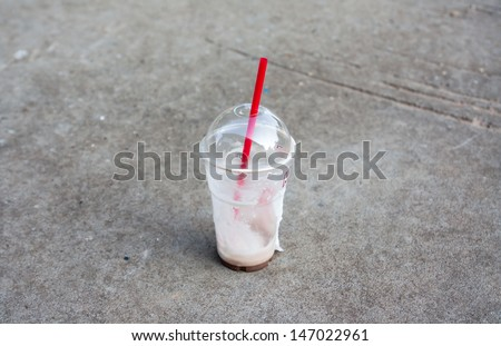 plastic coffee cup  on ground - stock photo