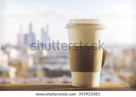 Plastic coffee cup with sunlit city in the background. Mock up - stock photo