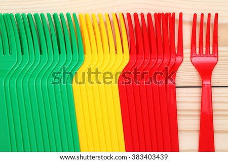 plastic colorful forks on wood background - stock photo
