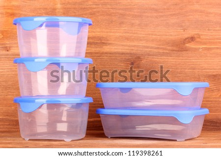 Plastic containers for food on wooden background - stock photo