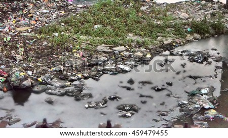 Plastic Contamination into Nature. Garbage and bottles floating on water. Environmental pollution. Garbage in the water of river.