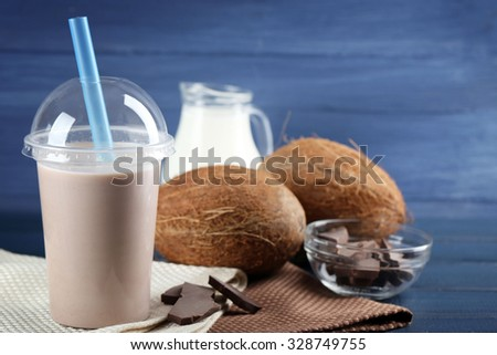 Plastic cup of milkshake on color wooden background - stock photo