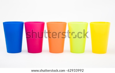 Plastic cups of various color isolated on white. - stock photo