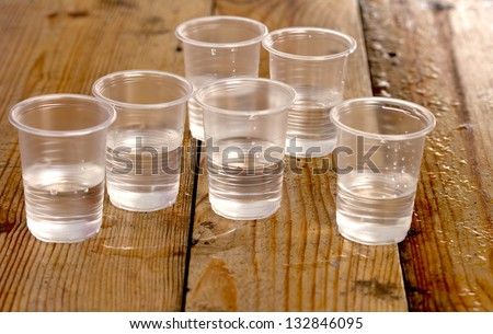 plastic cups of water on the wooden background - stock photo