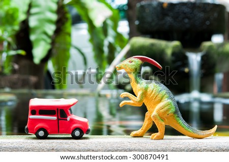 plastic dinasaur and red bus toy model - stock photo