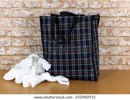 Plastic disposable bags and environmentally friendly re- usable tartan bag with a brick wall background - stock photo