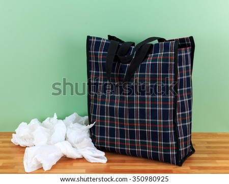 Plastic disposable bags and environmentally friendly  re- usable tartan bag with a green  wall background - stock photo