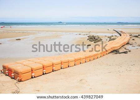 Plastic dock orange on beach on tide landscape sea background - stock photo