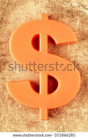 Plastic dollar symbol on canvas background - stock photo