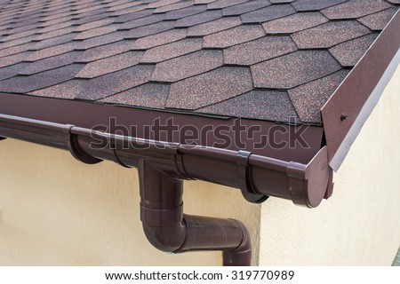 plastic drainage on the roof near the shingles - stock photo