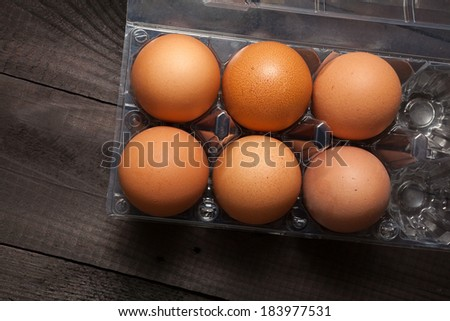 Plastic egg box with six brown eggs - stock photo