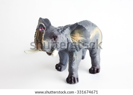 Plastic elephant toy isolated in front of a white background, angle view. - stock photo