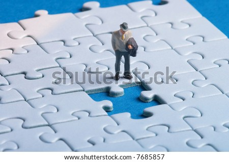 plastic figure standing in front of a hole in a puzzle - stock photo