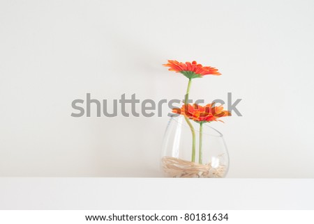 Plastic flowers in glass close, white background up shoot. - stock photo