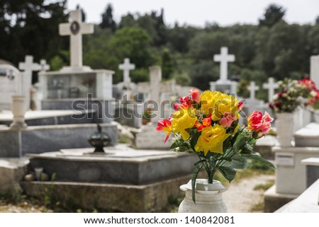 Plastic flowers on a greek cemetery with shallow DOF - stock photo