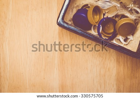plastic garbage in a terracotta container on a wood background
