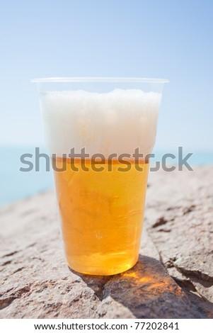 Plastic glass of beer on rock - stock photo