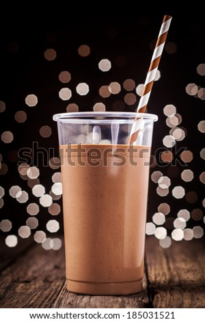 Plastic glass of delicious creamy chocolate smoothie or milkshake against a background of sparkling festive party lights - stock photo