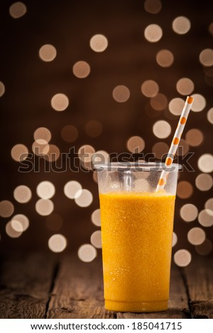 Plastic glass of tasty refreshing chilled tropical orange mango smoothie standing on a wooden counter overlooking a twinkling bokeh of party lights with copyspace - stock photo