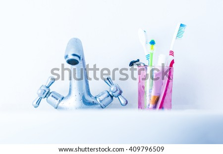Plastic glass with toothbrushes on basin near water tap - stock photo