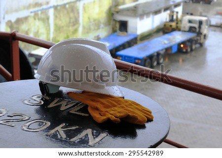 plastic helmet and gloves lying on the ship's bitts in the rain - stock photo