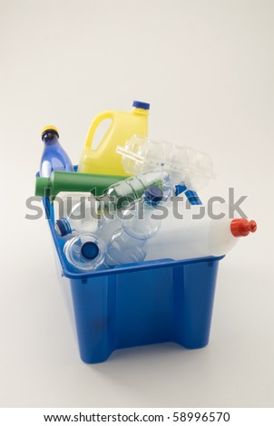 Plastic household materials in a blue recycling bin. White background.