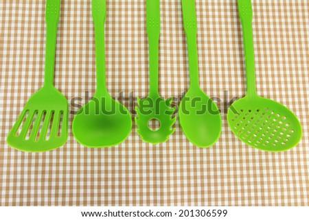 Plastic kitchen utensils on fabric background - stock photo
