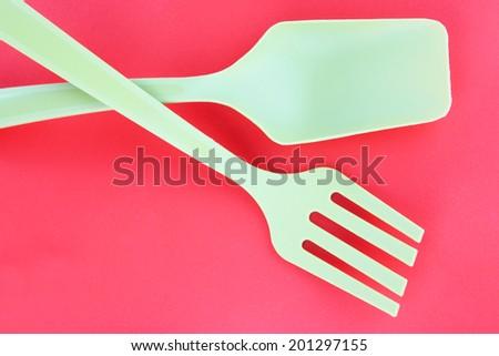 Plastic kitchen utensils on red background - stock photo