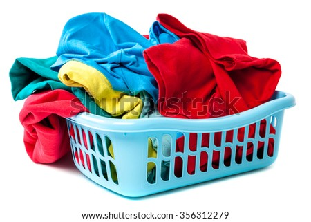Plastic laundry basket with clothes isolated on a white background.