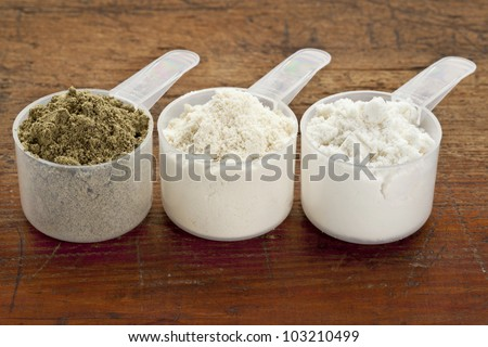 plastic measuring sccps of three protein powders (from left hemp seed, whey concentrate, whey isolate) on a grunge wood surface - stock photo