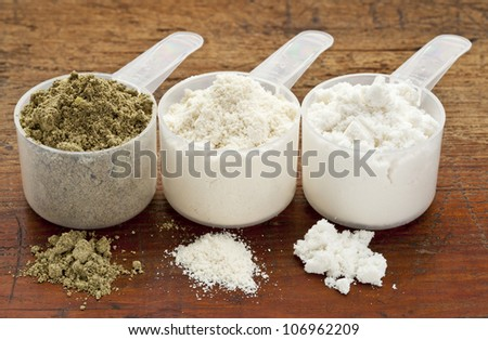 plastic measuring scoops of three protein powders (from left hemp seed, whey concentrate, whey isolate) on a grunge wood surface - stock photo