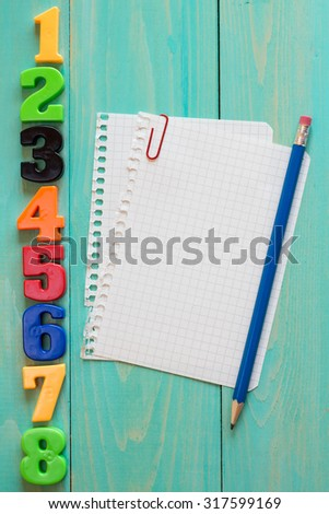 Plastic numbers and empty notebook with pencil