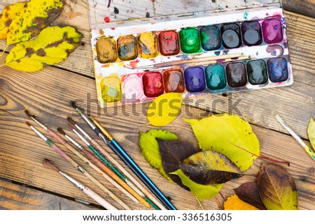 Plastic paint palette with paint, brushes and yellow leaves on wooden table - stock photo