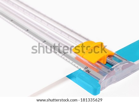 Plastic paper cutter with sliding blade handle ready to cut paper. Ruler in inches for precision measurment and a straight edge. Office hand tool concept. Horizontal photo.  - stock photo