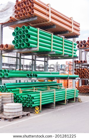 Plastic pipes stacked in a factory or warehouse yard for use in plumbing or sewage installations on a construction site - stock photo