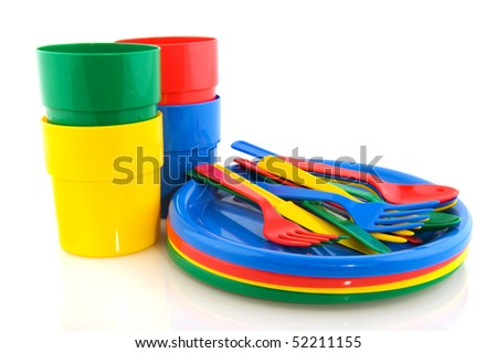 Plastic plates mugs and forks spoons and knifes in colorful plastic
