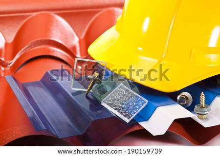 Plastic polycarbonate roof shapes, screws for fixing and yellow hard hat - stock photo