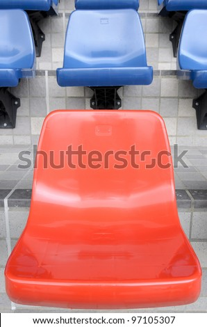 Plastic red and blue new chairs in stadium - stock photo