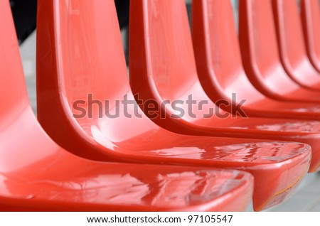 Plastic red new chairs in stadium - stock photo