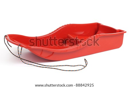 Plastic red sled for skiing on white background - stock photo