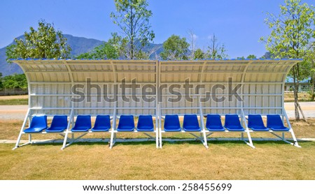 Plastic seats on outdoor stadium players bench. - stock photo