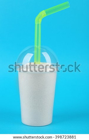 Plastic smoothie cup with granulated sugar and cocktail tube on blue background