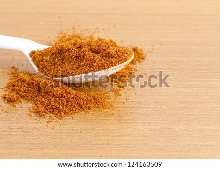 Plastic spoon full of dried paprika  on wooden worktop - stock photo