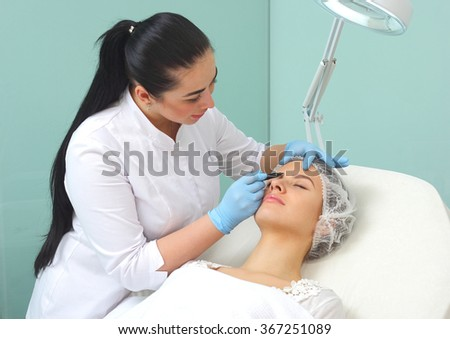 Plastic surgeon drawing lines over eyelid of a nice young female before cosmetic operation. - stock photo
