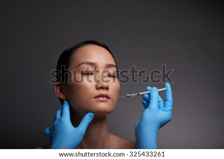 Plastic surgeon making anesthetic injection into face of female patient