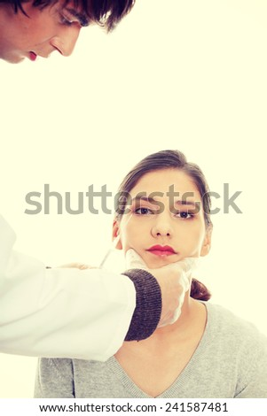 Plastic surgeons giving botox injection in female skin. - stock photo