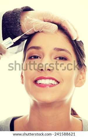 Plastic surgeons giving injection in female skin. - stock photo