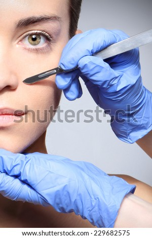Plastic surgery, a woman in the clinic of aesthetic surgery.Caucasian woman during surgery using a scalpel - stock photo
